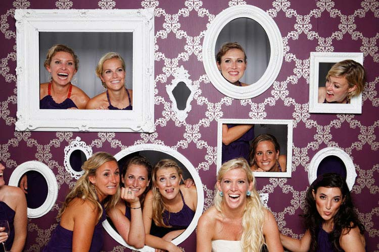 group of women holding up photo booth frames around their faces