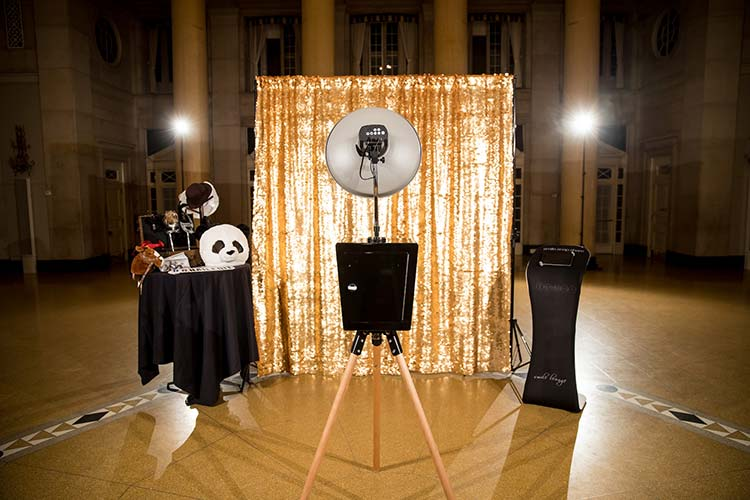 An empty ballroom with a stand alone photo booth unit staged with props